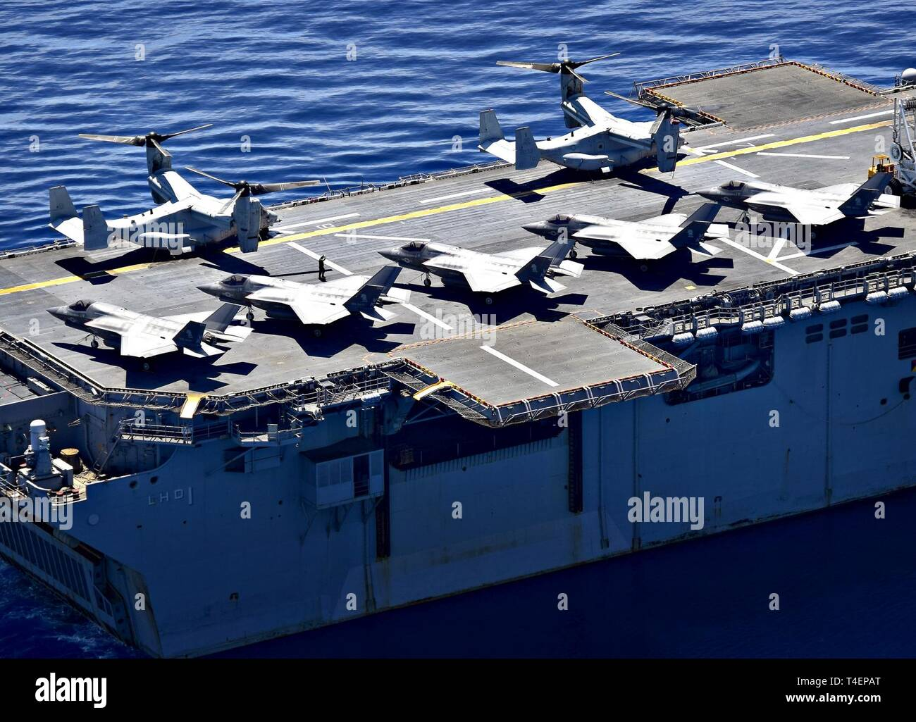 SOUTH CHINA SEA (March 29, 2019) F-35B Lightning II aircraft, assigned to Marine Fighter Attack Squadron (VMFA) 121, and MV-22 Osprey, assigned to Marine Medium Tiltrotor Squadron (VMM) 268, are secured to the flight deck aboard the amphibious assault ship USS Wasp (LHD 1). Wasp, flagship of Wasp Amphibious Ready Group, is operating in the Indo-Pacific region to enhance interoperability with partners and serve as a lethal, ready-response force for any type of contingency. - Stock Image