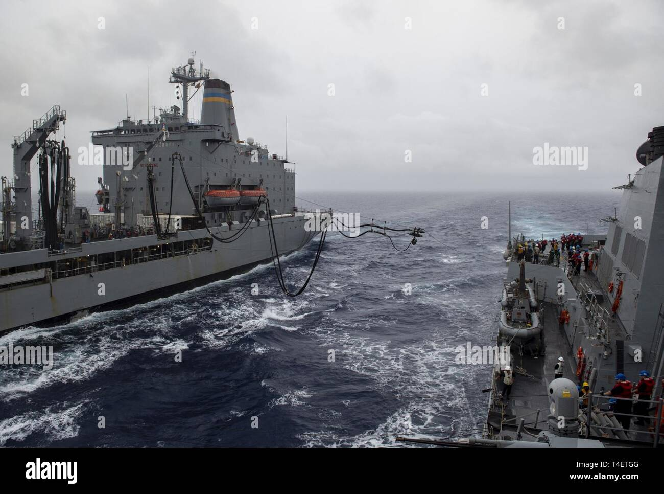 SOUTH CHINA SEA (April 03, 2019) The Arleigh Burke-class guided-missile destroyer USS Preble (DDG 88) receives a fueling probe from the Military Sealift Command fleet replenishment oiler USNS Guadalupe (T-AO 200) during a replenishment-at-sea. Preble is deployed to the U.S 7th Fleet area of operations in support of security and stability in the Indo-Pacific region. - Stock Image