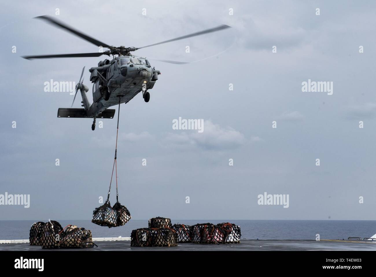 SOUTH CHINA SEA (April 4, 2019) –  An MH-60S Sea Hawk assigned to Helicopter Sea Combat Squadron (HSC) 25 lowers supplies onto the flight deck of the amphibious assault ship USS Wasp (LHD 1) during a replenishment-at-sea during Exercise Balikatan 2019. Exercise Balikatan, in its 35th iteration, is an annual U.S., Philippine military training exercise focused on a variety of missions, including humanitarian assistance and disaster relief, counter-terrorism, and other combined military operations. - Stock Image