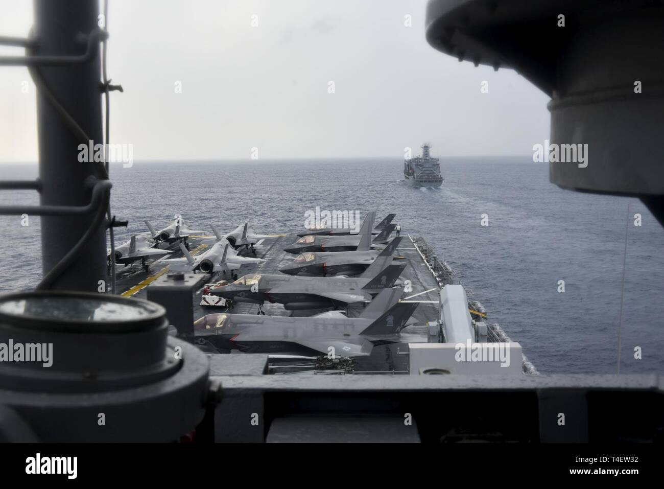 SOUTH CHINA SEA (April 4, 2019) - The amphibious assault ship USS Wasp (LHD 1) approaches the fleet replenishment oiler USNS Pecos (T-AO 197) during a replenishment-at-sea during Exercise Balikatan 2019. Exercise Balikatan, in its 35th iteration, is an annual U.S., Philippine military training exercise focused on a variety of missions, including humanitarian assistance and disaster relief, counter-terrorism, and other combined military operations. - Stock Image
