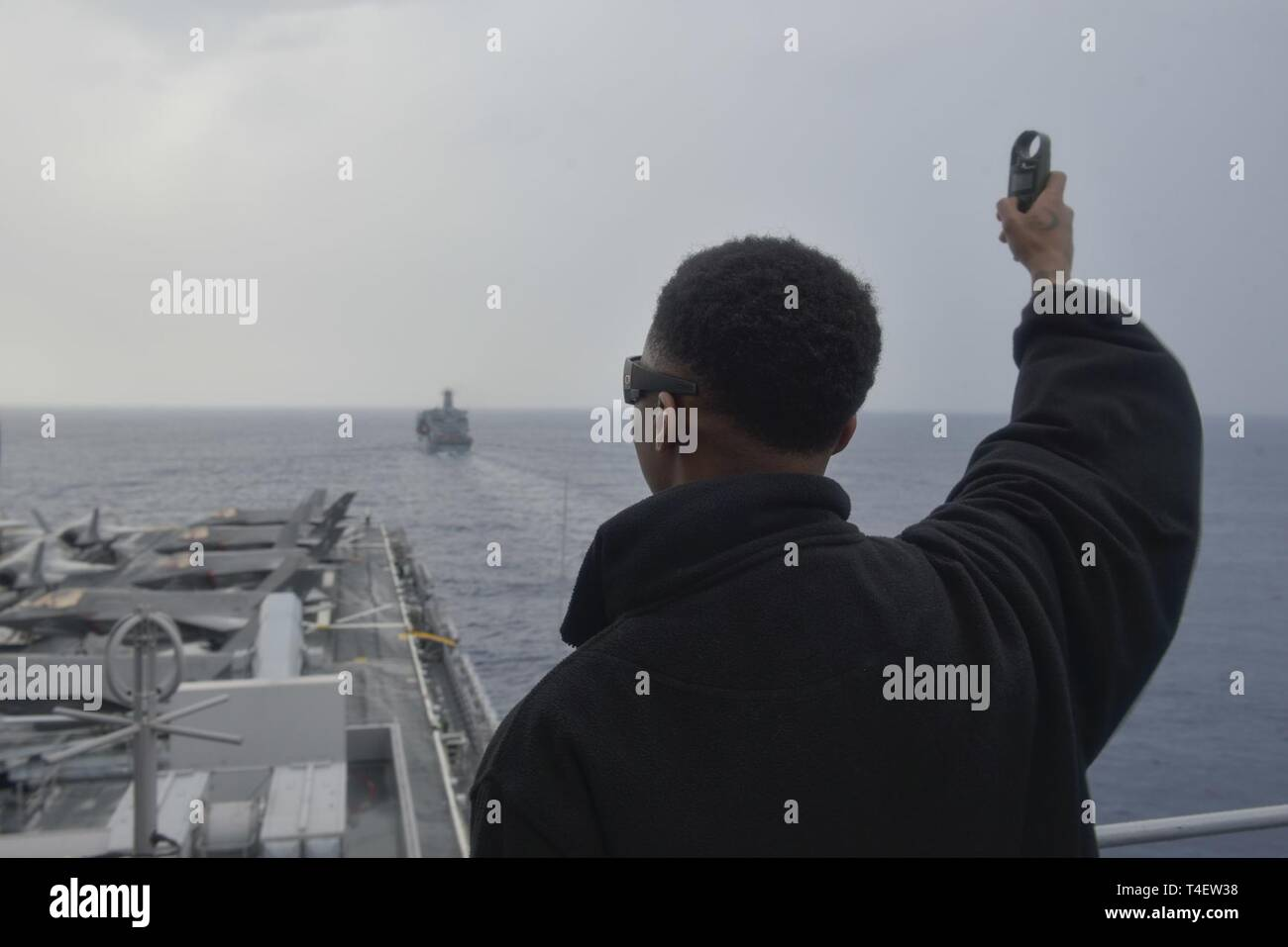 SOUTH CHINA SEA (April 4, 2019) - Aerographer's Mate Airman Braxton Reese, from Jacksonville, Fla., measures wind speed onboard the amphibious assault ship USS Wasp (LHD 1) during a replenishment-at-sea with the fleet replenishment oiler USNS Pecos (T-AO 197) during Exercise Balikatan 2019. Exercise Balikatan, in its 35th iteration, is an annual U.S., Philippine military training exercise focused on a variety of missions, including humanitarian assistance and disaster relief, counter-terrorism, and other combined military operations. - Stock Image
