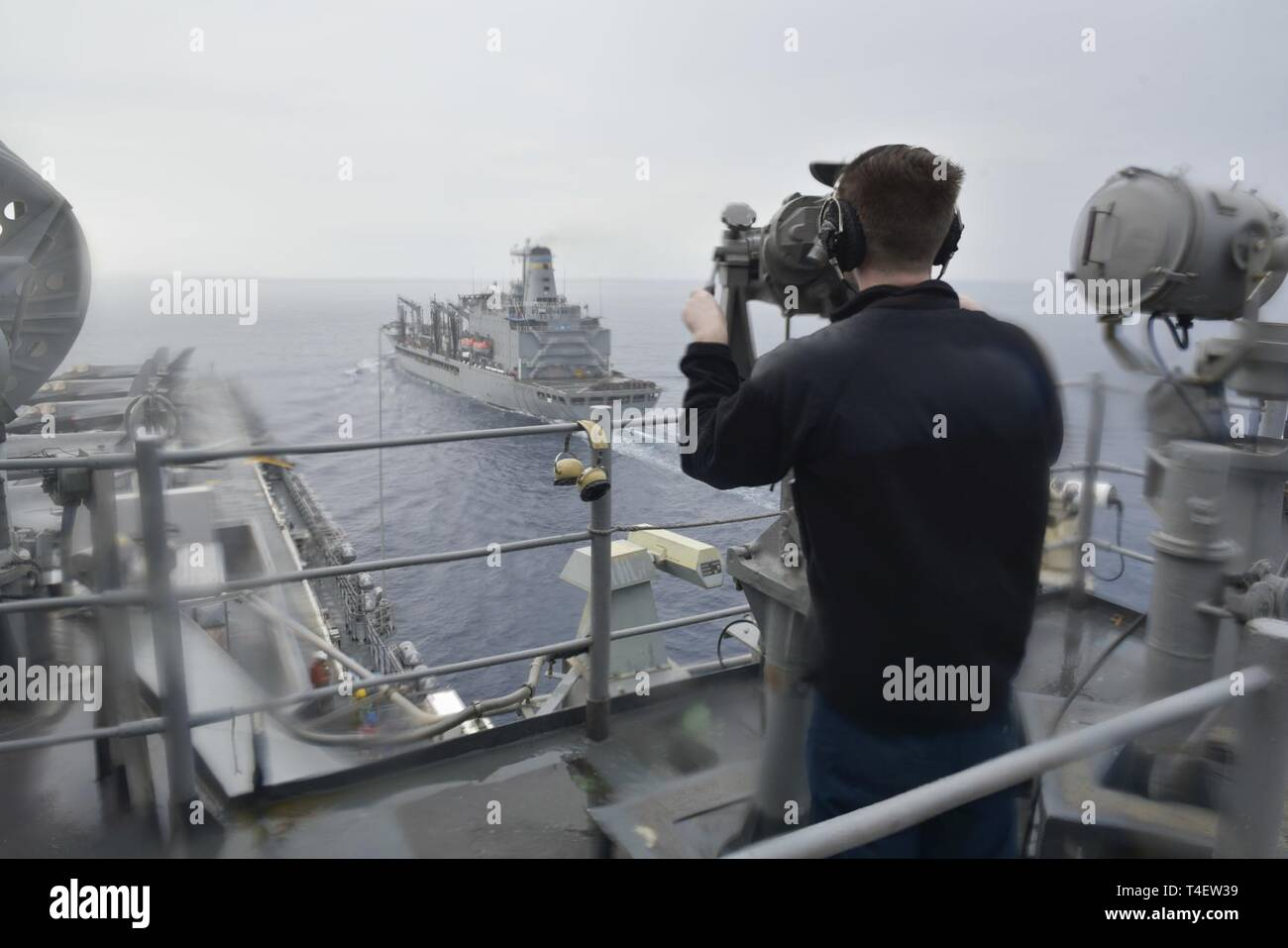 SOUTH CHINA SEA (April 4, 2019) - Operations Specialist Seaman George Allen, from Columbus, Ohio, stands watch onboard the amphibious assault ship USS Wasp (LHD 1) during a replenishment-at-sea  with the fleet replenishment oiler USNS Pecos (T-AO 197) during Exercise Balikatan 2019. Exercise Balikatan, in its 35th iteration, is an annual U.S., Philippine military training exercise focused on a variety of missions, including humanitarian assistance and disaster relief, counter-terrorism, and other combined military operations. - Stock Image