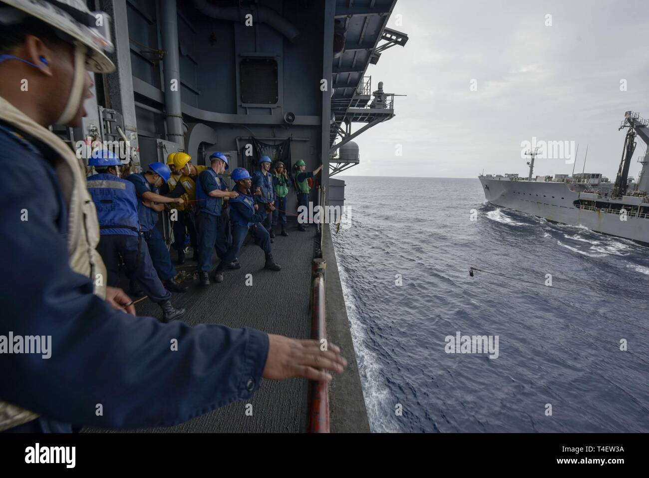 SOUTH CHINA SEA (April 4, 2019) - Sailors assigned to the amphibious assault ship USS Wasp (LHD 1) heave line during a replenishment-at-sea with the replenishment oiler USNS Pecos (T-AO 197) during Exercise Balikatan 2019. Exercise Balikatan, in its 35th iteration, is an annual U.S., Philippine military training exercise focused on a variety of missions, including humanitarian assistance and disaster relief, counter-terrorism, and other combined military operations. - Stock Image
