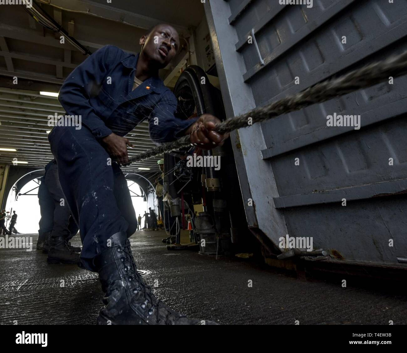 SOUTH CHINA SEA (April 4, 2019) - Seaman Vincent Nsiah, from Brooklyn, N.Y., heaves line onboard the amphibious assault ship USS Wasp (LHD 1) during a replenishment-at-sea with the fleet replenishment oiler USNS Pecos (T-AO 197) during Exercise Balikatan 2019. Exercise Balikatan, in its 35th iteration, is an annual U.S., Philippine military training exercise focused on a variety of missions, including humanitarian assistance and disaster relief, counter-terrorism, and other combined military operations. - Stock Image