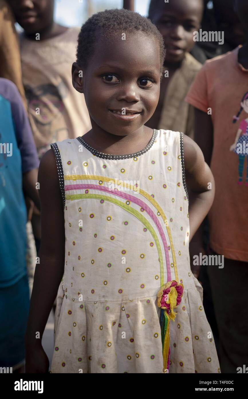 A little girl poses for a picture as her parents wait for food aid to be distributed in Nhagau, Mozambique, April 6, 2019. Combined Joint Task Force-Horn of Africa is helping meet requirements identified by U.S. Agency for International Development (USAID) assessment teams and humanitarian organizations working in the region by providing logistics support and manpower to USAID at the request of the Government of the Republic of Mozambique. - Stock Image