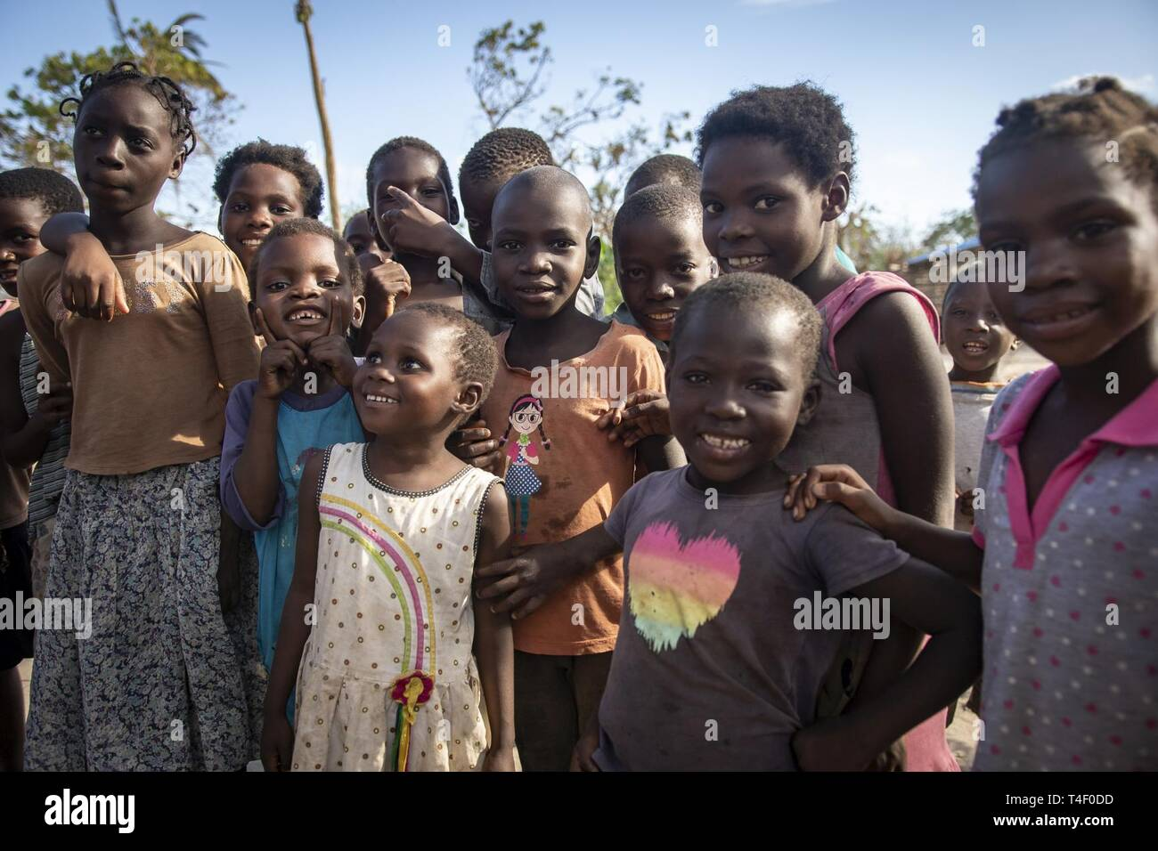 Children pose for a picture as their parents wait for food aid to be distributed in Nhagau, Mozambique, April 6, 2019. Combined Joint Task Force-Horn of Africa is helping meet requirements identified by U.S. Agency for International Development (USAID) assessment teams and humanitarian organizations working in the region by providing logistics support and manpower to USAID at the request of the Government of the Republic of Mozambique. - Stock Image