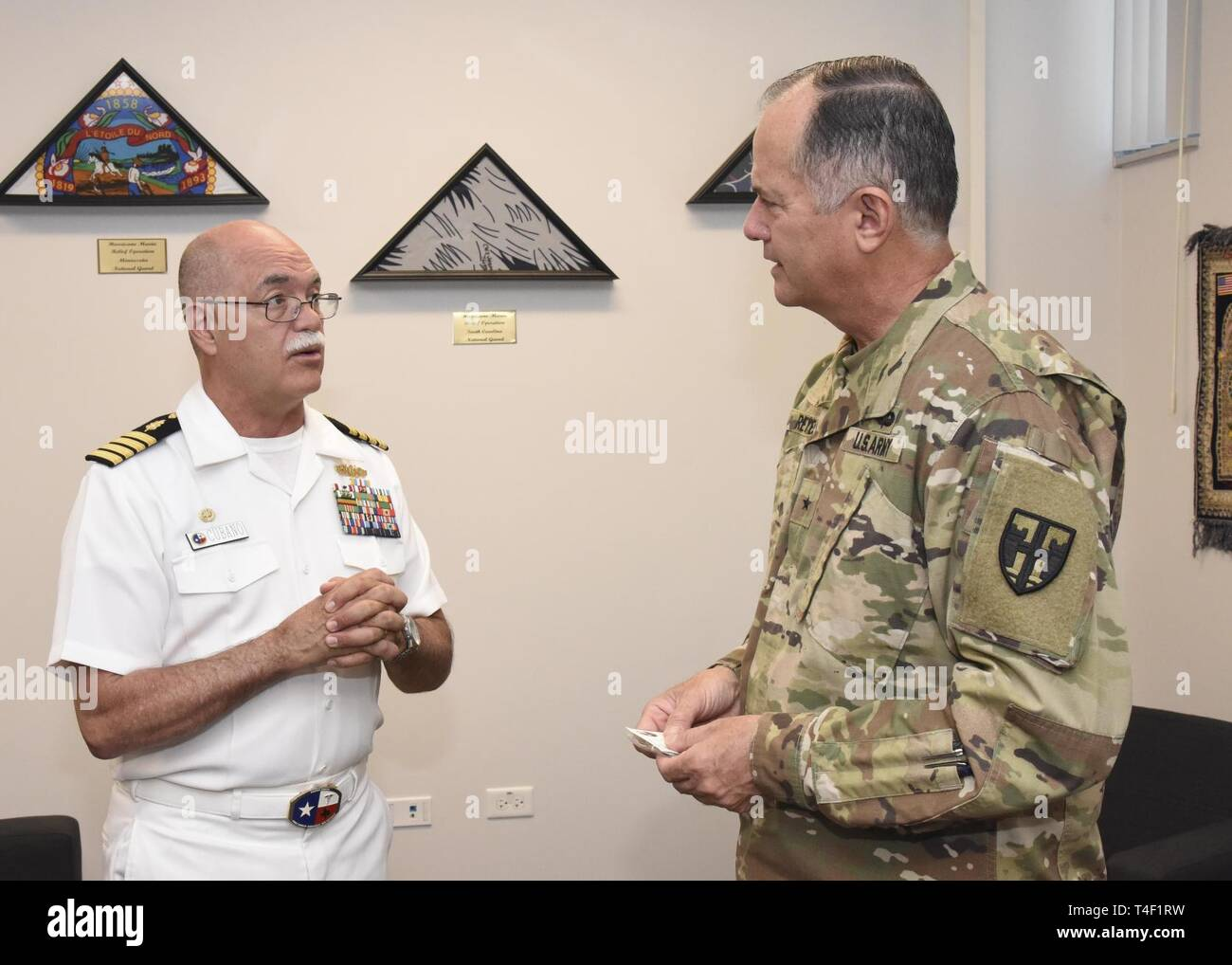 SAN JUAN, Puerto Rico. (April 8, 2019) U.S. Navy Capt. Miguel Cubano, commanding officer, Naval Health Clinic Corpus Christi, Texas, speaks with Puerto Rico National Guard Brig. Gen. Jose Reyes about Navy Week Puerto Rico.  Navy Weeks focus a variety of outreach assets, equipment and personnel on a single city for a week-long series of engagements with key influencers and organizations representing all sectors of the market.  During a Navy Week, 75-100 outreach events are coordinated with corporate, civic, government, education, media, veterans, community service and diversity organizations in - Stock Image