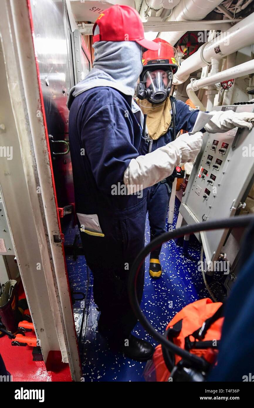 SEA (April 8, 2019) - Electrician's Mate 3rd Class Francis Murray sets electrical isolation during a main space fire drill aboard the Arleigh Burke-class guided-missile destroyer USS Ross (DDG 71) in the Mediterranean Sea, April 8, 2019. Ross, forward-deployed to Rota, Spain, is on its eighth patrol in the U.S. 6th Fleet area of operations in support of U.S. national security interests Europe and Africa. - Stock Image