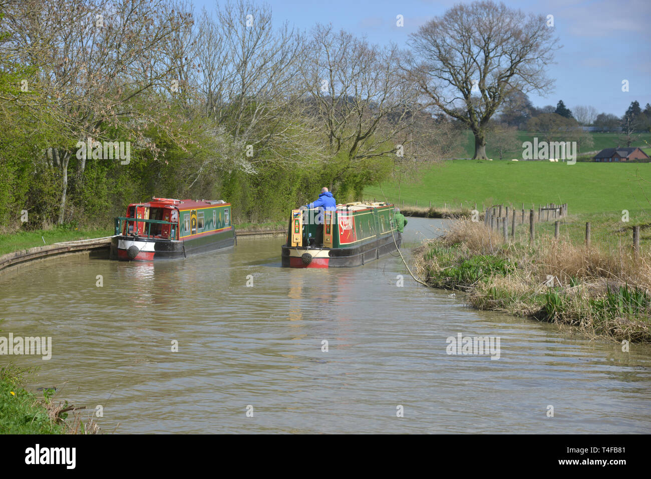 The Oxford Canal meanders through the Warwickshire countryside near the village of Wormleighton as a narrow boat sails along it. Stock Photo