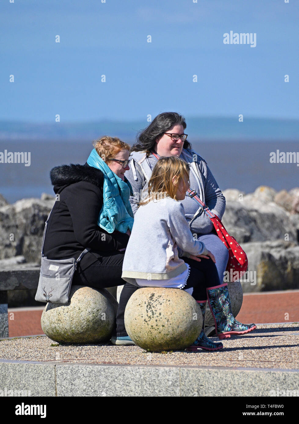 Three females sitting on stone seats, in Spring sunshine. Stone Jetty, Promenade, Morecambe, Lancashire, England, United Kingdom, Europe. Stock Photo