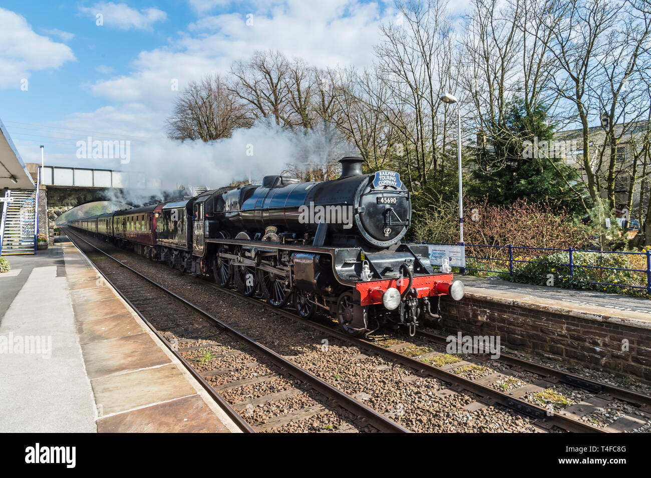 The image shows the LMS Jubilee Class 6P 4-6-0 nos 45690 Leander steam train passing through Bentham Station on the Lancaster-Leeds Line - Stock Image
