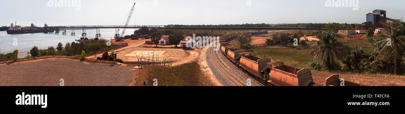 Rail & port operations for managing and transporting iron ore. Ship at loading jetty at end of conveyor belt & ore train on rail loop after discharge. Stock Photo