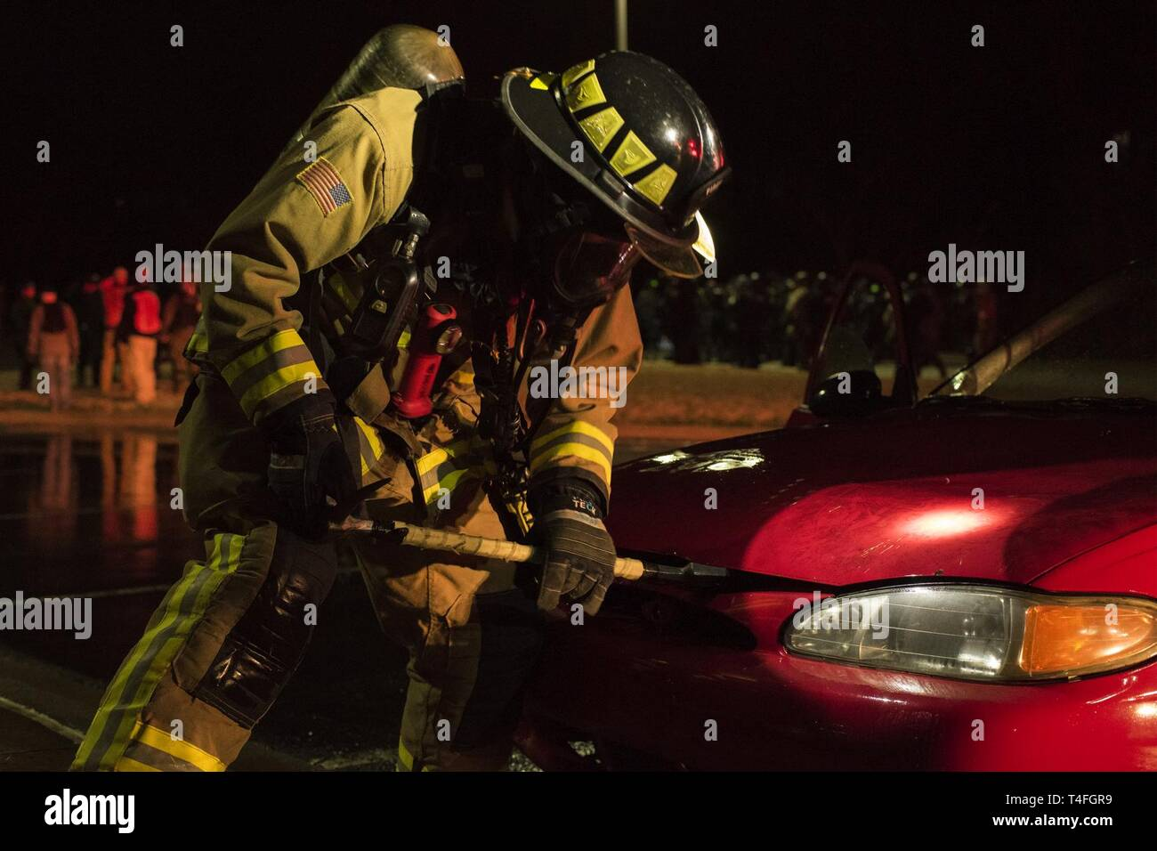 A firefighter assigned to Little Rock Air Force Base, Arkansas, practices dousing a car fire during Operation Phalax held March 30-31, 2019.  The operation is a joint exercise hosted by the Arkansas National Guard for civil and military organizations to train their members in tactics and techniques used in responding to a civil disturbance. - Stock Image