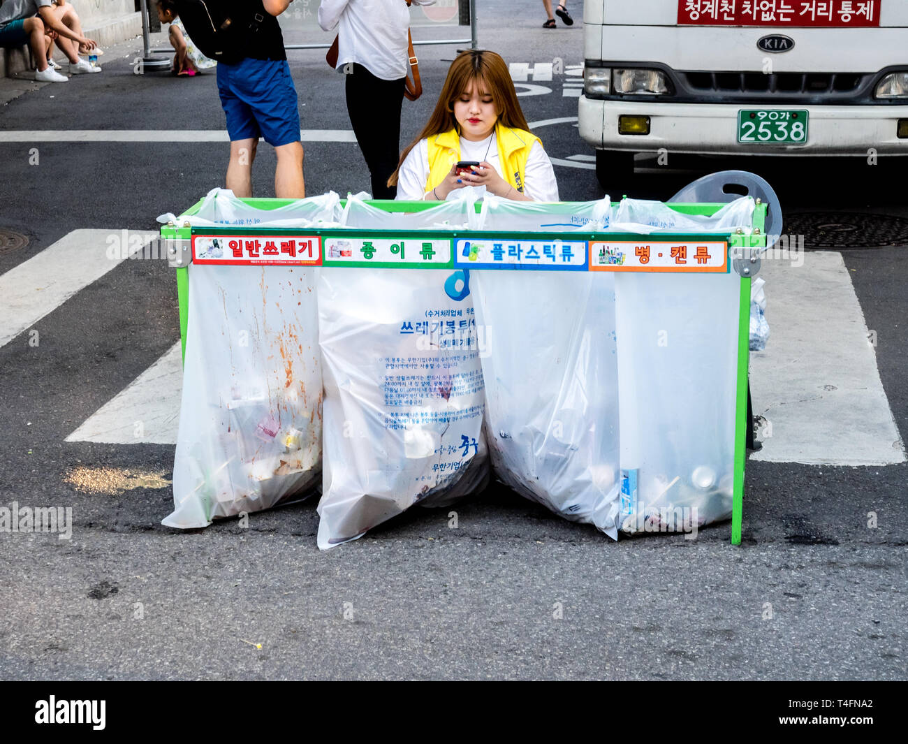 Seoul, South Korea - June 17, 2017: Woman sitting near waste sorting containers with colored inscriptions for plastic, glass bottles and paper. Stock Photo