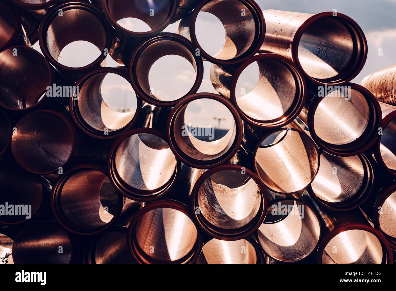Plastic sewer pipes on construction site for system repairing stacked and ready to be installed - Stock Image