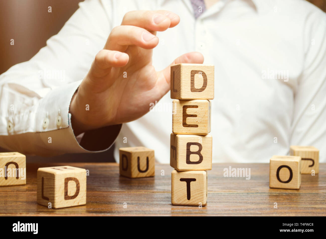 Businessman removes wooden blocks with the word Debt. Reduction or restructuring of debt. Bankruptcy announcement. Refusal to pay debts or loans and i - Stock Image