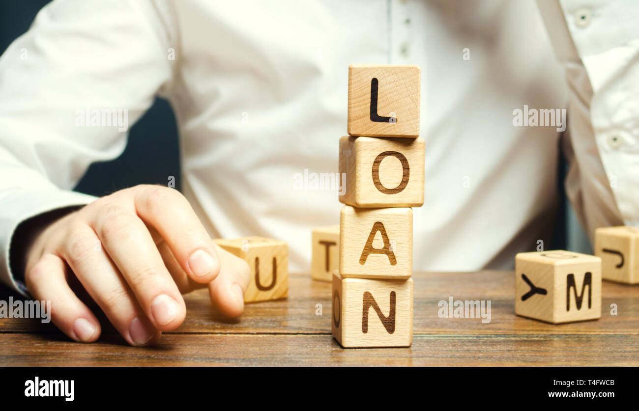 Wooden blocks with the word loan and businessman. Consumer, banking and property loan. Business and entrepreneurial development. Small business loans. - Stock Image