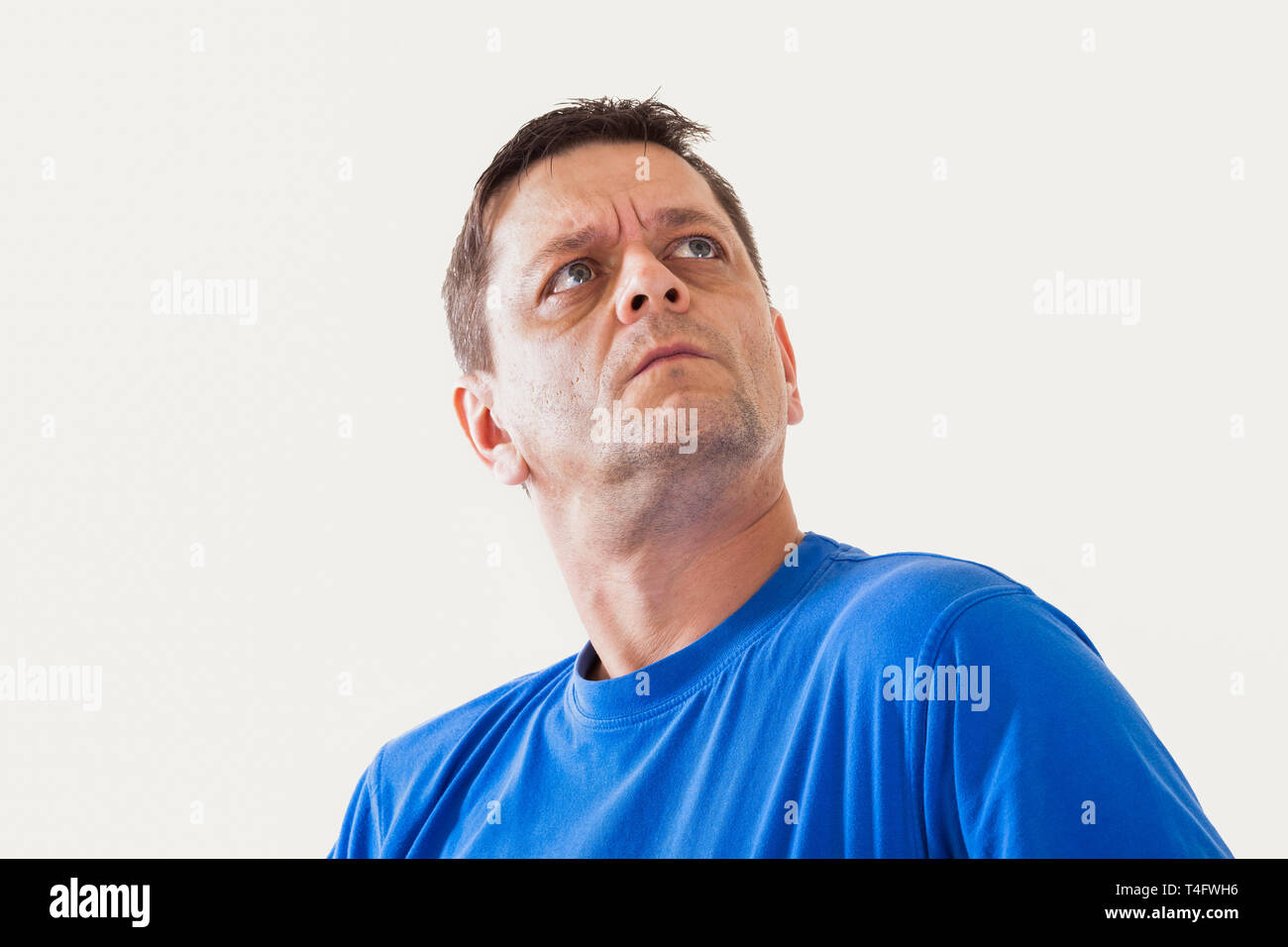 Portrait of a man of thoughtfully looks upwards - isolated - Stock Image