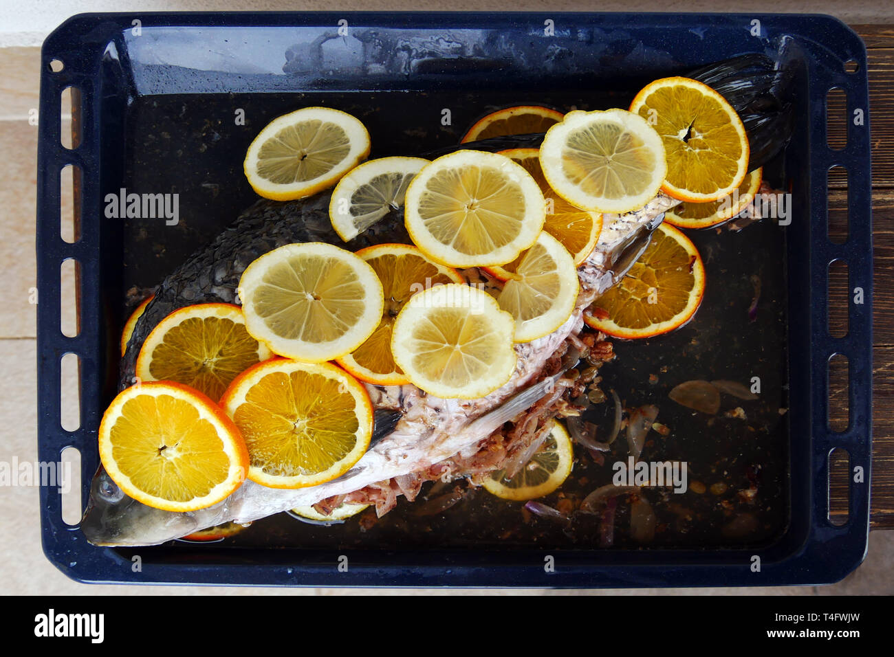 Prepared for  baking fish. Сarp filled with onions and walnutsand covered with slices of lemon and orange. Delicious homemade food. Stock Photo