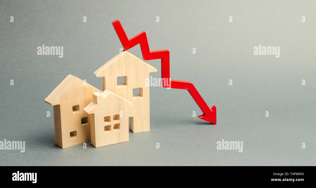 Miniature wooden houses and a red arrow down. The concept of low cost real estate. Lower mortgage interest rates. Falling prices for rental housing an Stock Photo