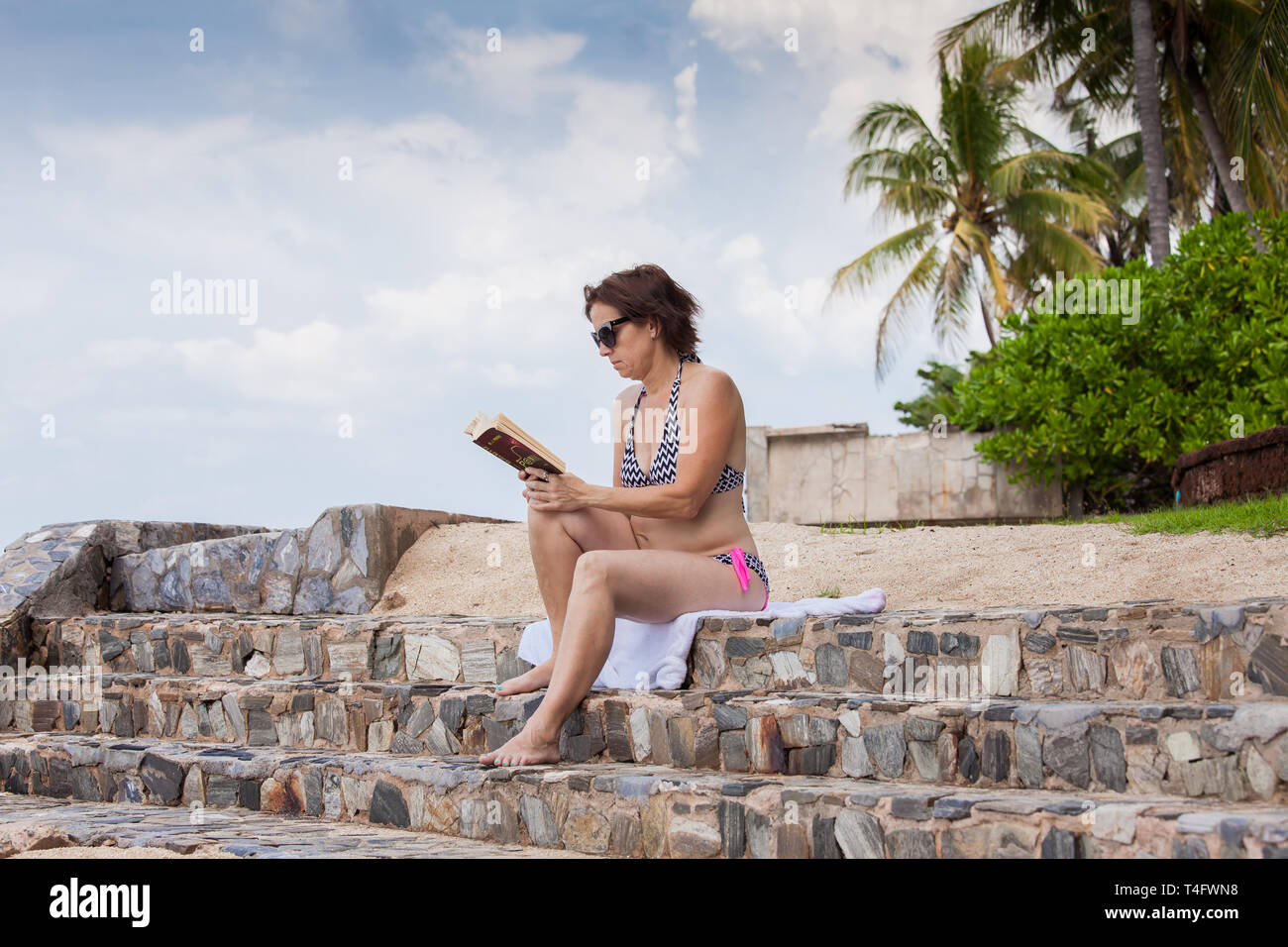 A middle-aged woman reading a book on a stone promenade. - Stock Image