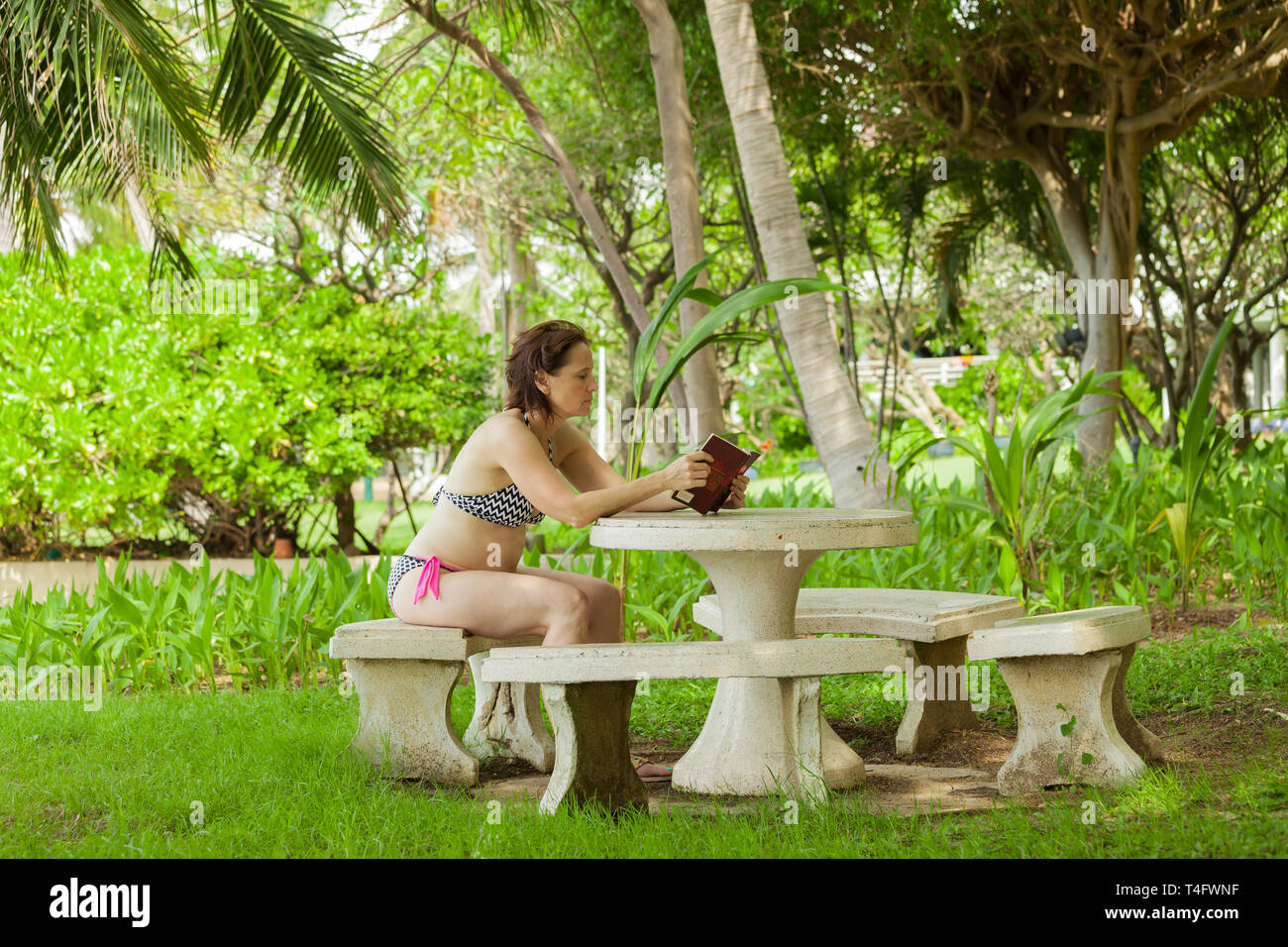 A woman reading a book in the garden with stone furniture. - Stock Image