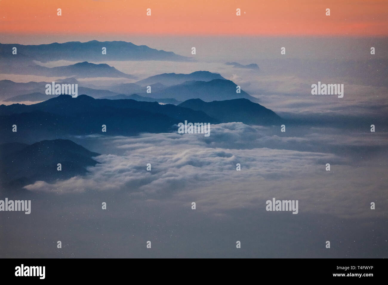 Photo of a high mountain peaks on the sunrise in Africa, Kilimanjaro.Red and peach colors of the sky, white clouds wrapping black mountain range. Peak Stock Photo