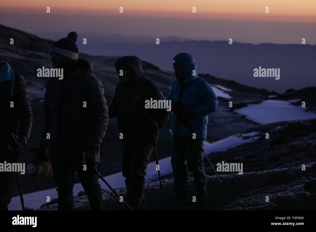 A group of tourists climbing on the Kilimanjaro mountain in Africa. Sunrise, red and yellow colors of the sun rays on the sky. Black peaks behind them Stock Photo