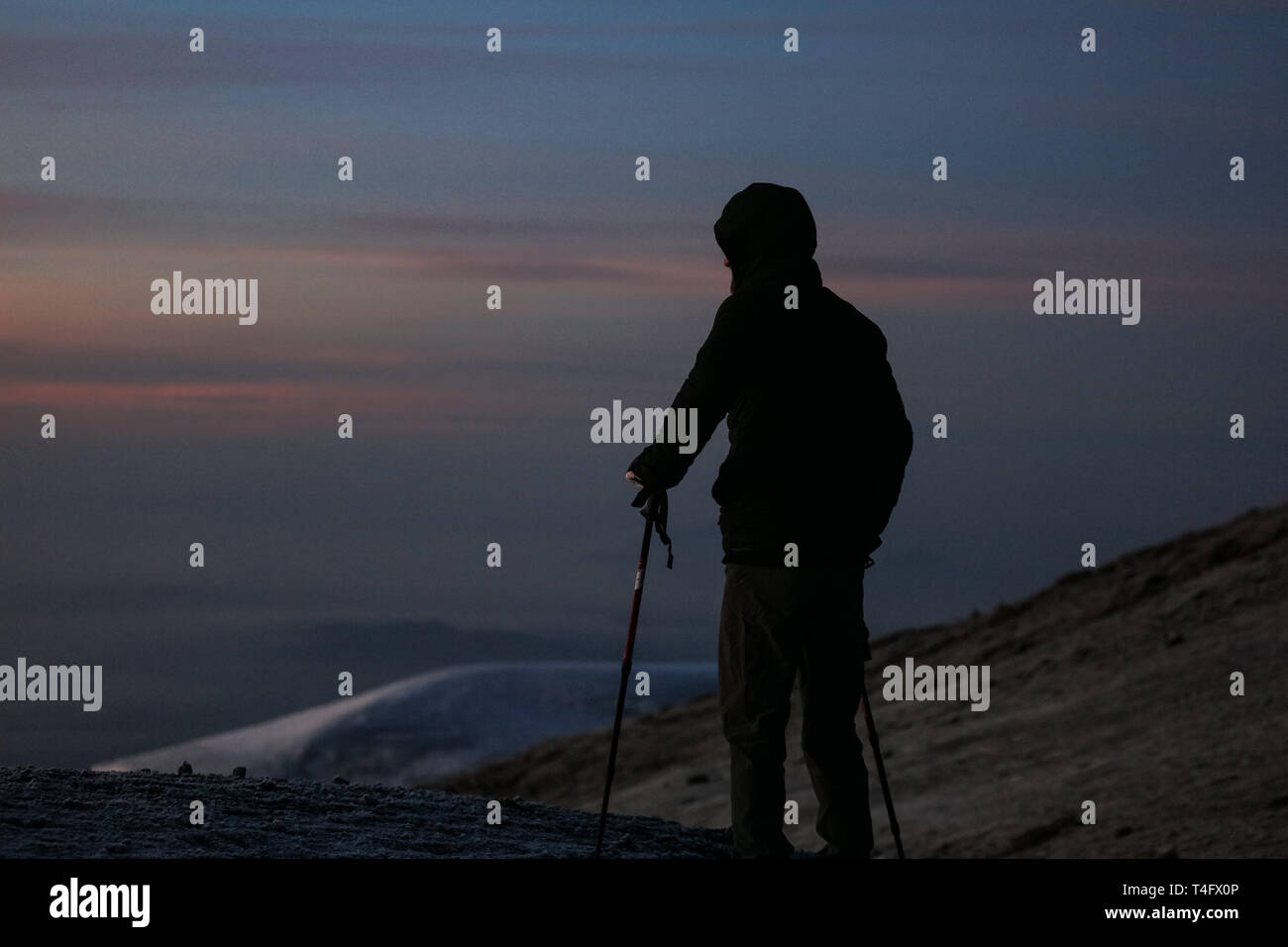Man in the black sportswear standing on the top of the Kilimanjaro in Africa. Enjoys the beautiful view of the mountains on the sunrise. High peaks Stock Photo