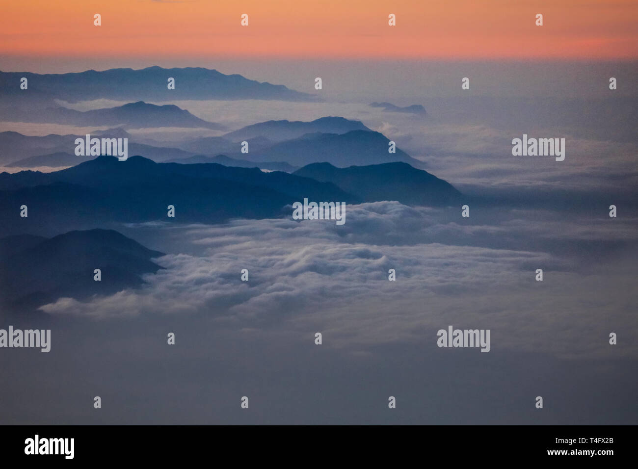 Dense white clouds covering high black peaks of the african mountains. New day begins with the sunlight coming up from the horizon. Stock Photo
