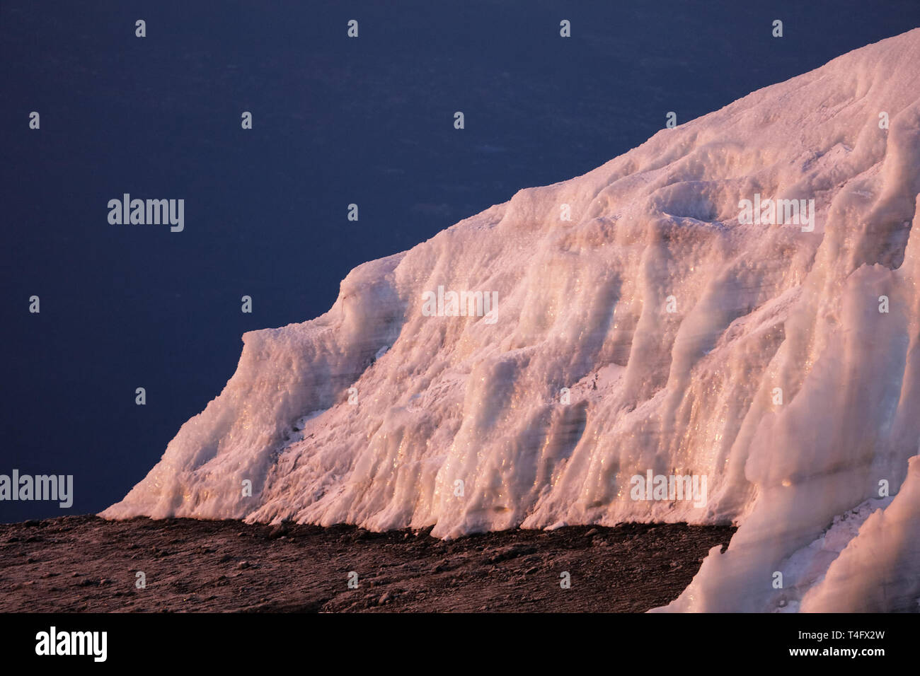 Blue dark sky and ground. Big ice and snow hill. Winter picture of the nature places. Stock Photo