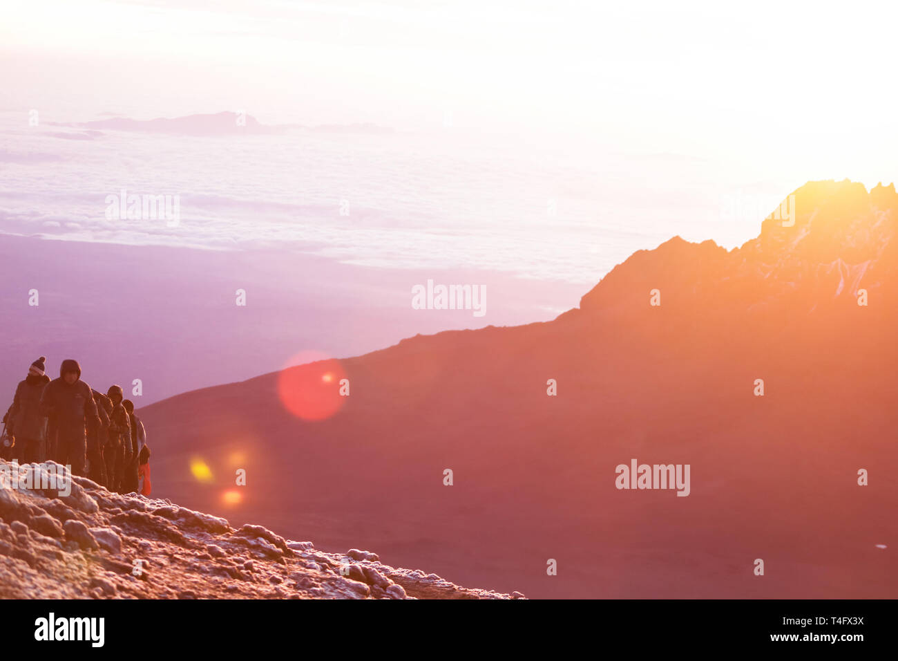 Incredible nature beauty, sunrise in the mountains. People climbing on the mountain top. Yellow warm light and freezing cold on the 5000 meters high. Stock Photo