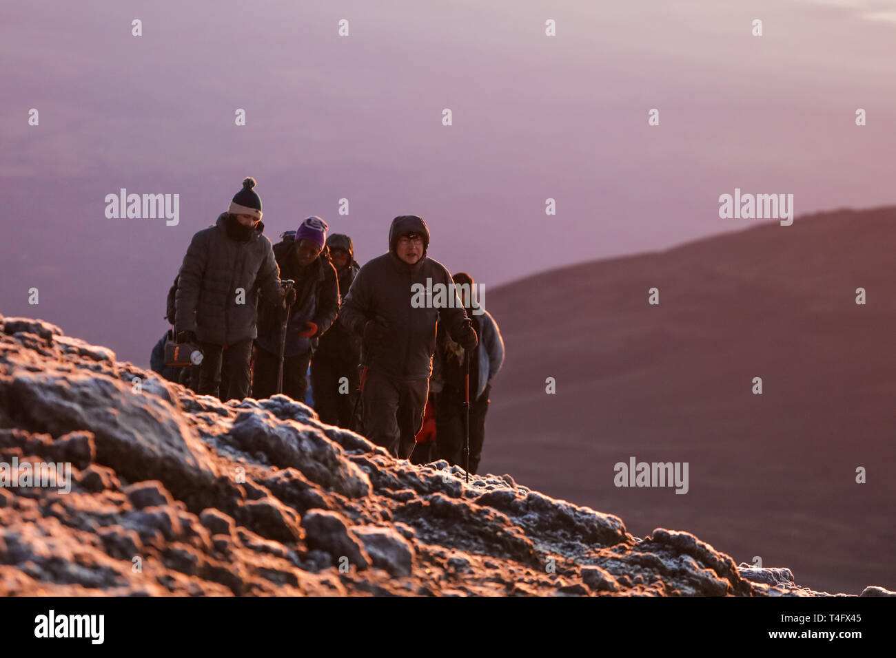 Strong men go through the rocks in Africa. Meet the sunrise on the mountain, cold wind and white snow. Brave and fearless people, extreme sport. View Stock Photo