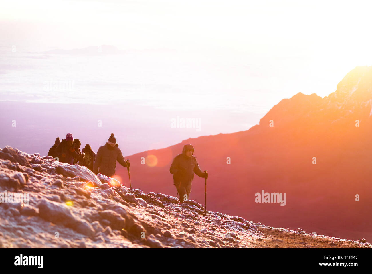 Bright sunshine in the mountains. Nature amazing landscape. Group of people climbing on the top of the Kilimanjaro. Cold wind and snow on the height Stock Photo