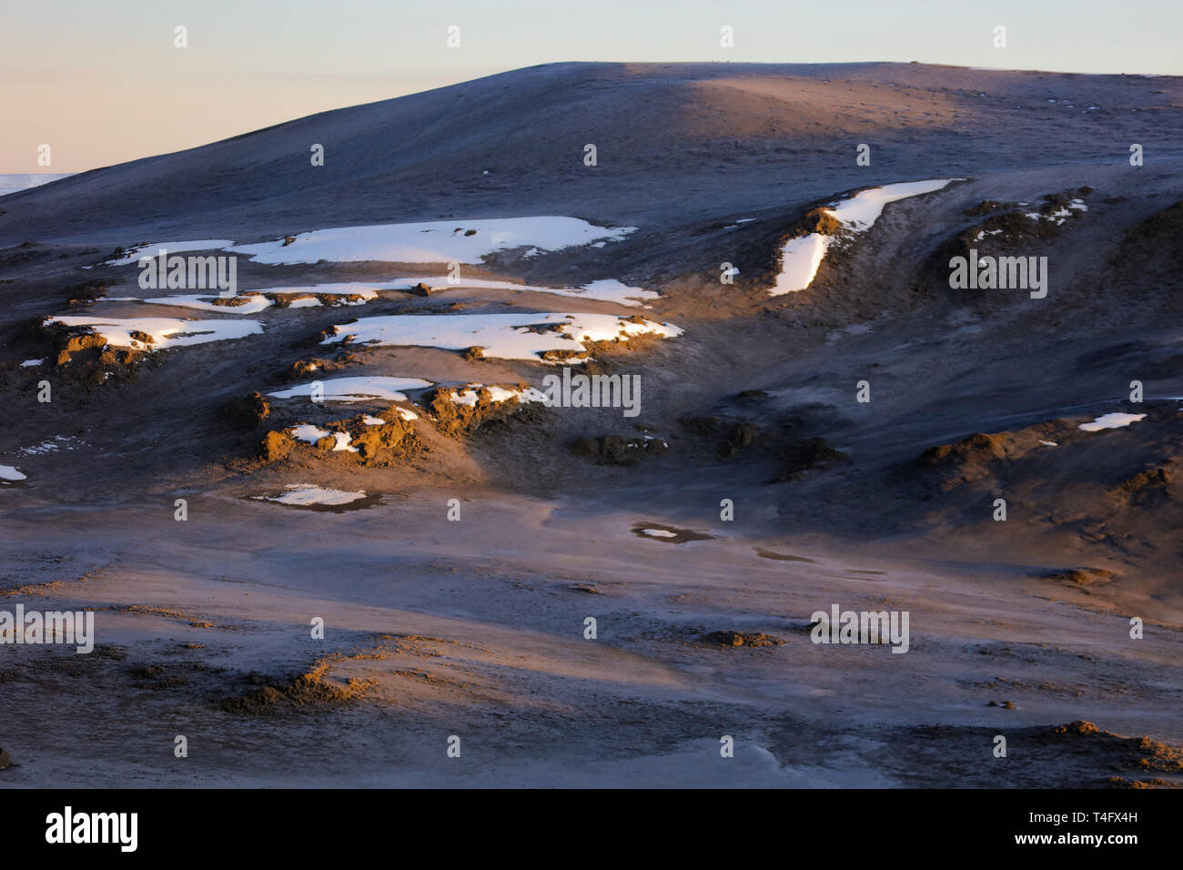 Soft morning light falling down on the surface of the african hill in a desert. Small rocks covered with snow. Winter sunrise on the Kilimanjaro.Climb Stock Photo