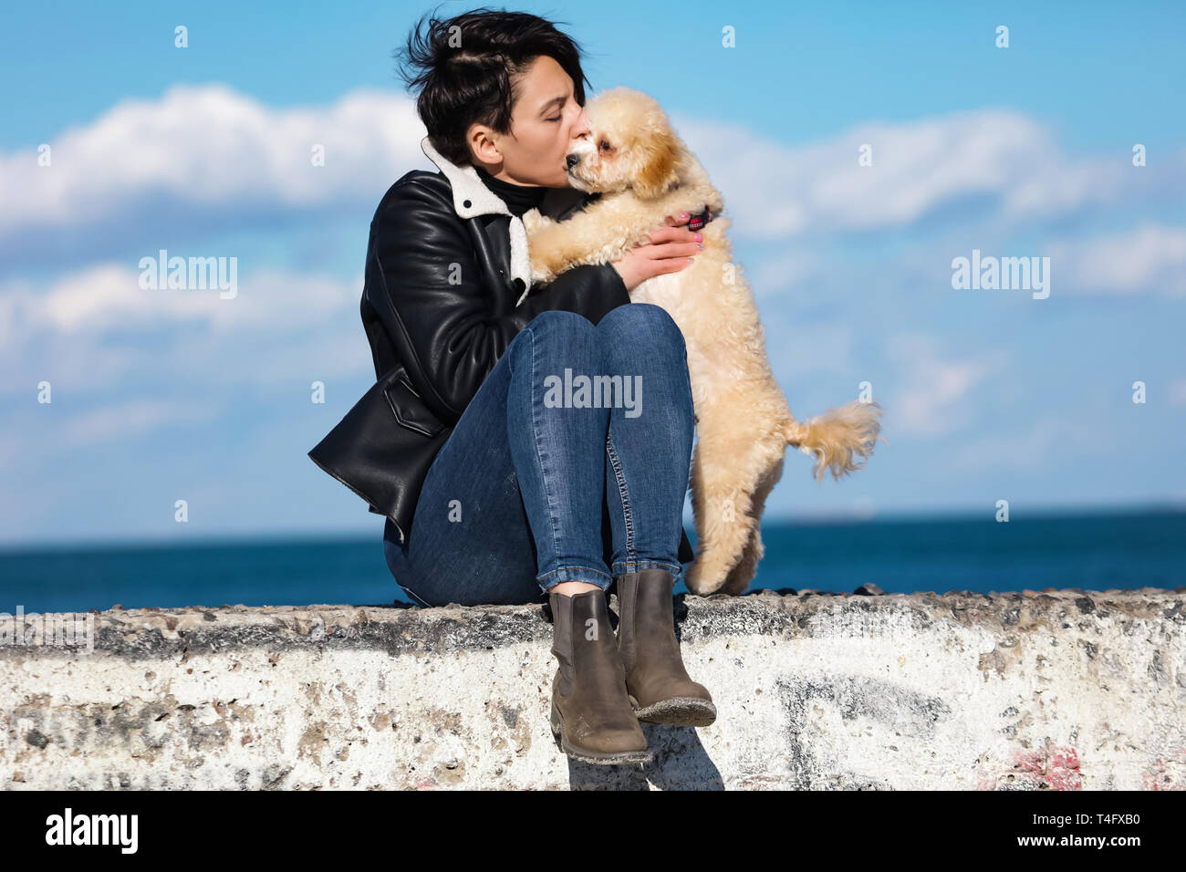 Tender woman holding her cute puppy and kissing him. Soft, curly fur, curved tail and black nose. Stylish haircut, modern leather jacket and jeans Stock Photo