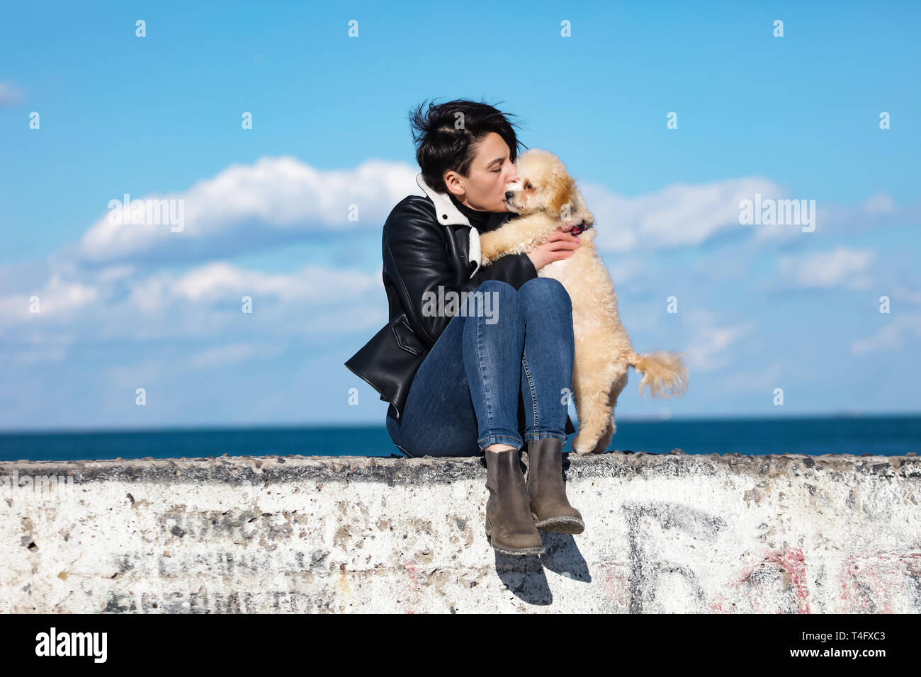 Cheerful young woman having fun on the pier with her little puppy, kissing and hugging him. Sea breeze, sunny spring weather. Blue sky and sea waves Stock Photo