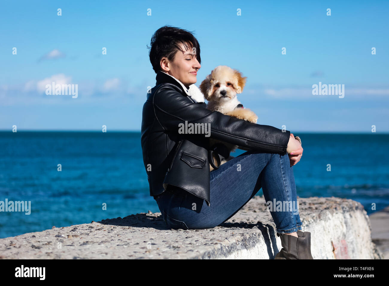 Calm and happy sunny day, woman sitting on the beach with her fluffy friend. Small puppy with curly fur and tiny black nose, love his owner and playin Stock Photo