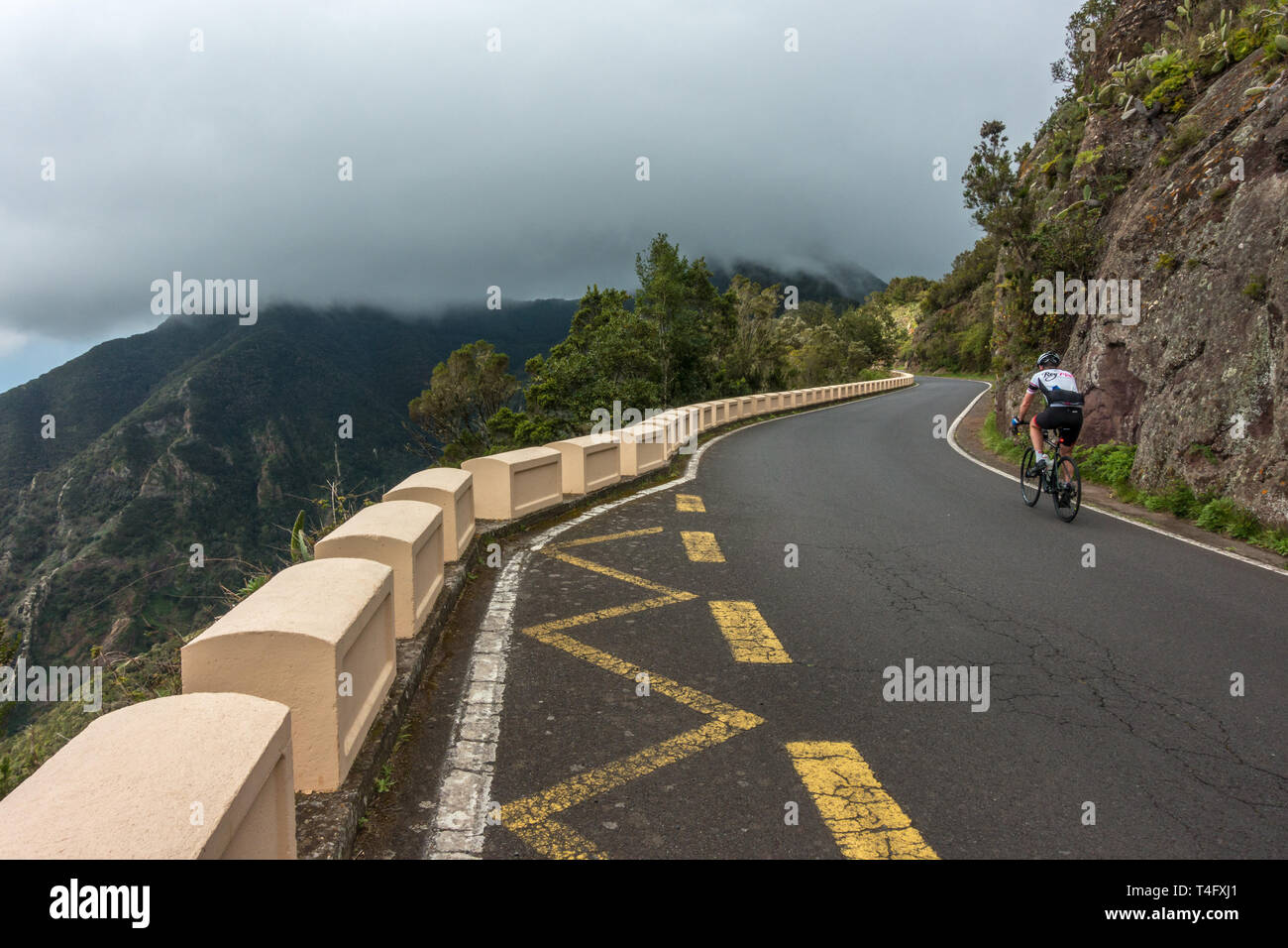 Dramatic mountain view of a cyclist on a road bike under the cloud in the Parque Rural de Anaga park, on the TF-12 road, Tenerife Stock Photo