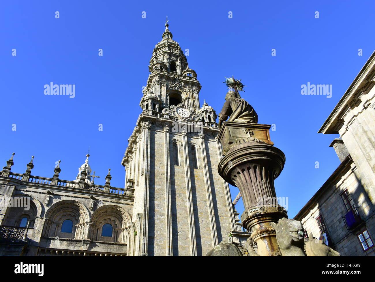 Cathedral, romanesque Platerias facade and baroque clock tower with stone horses fountain and blue sky. Santiago de Compostela, Spain. Stock Photo