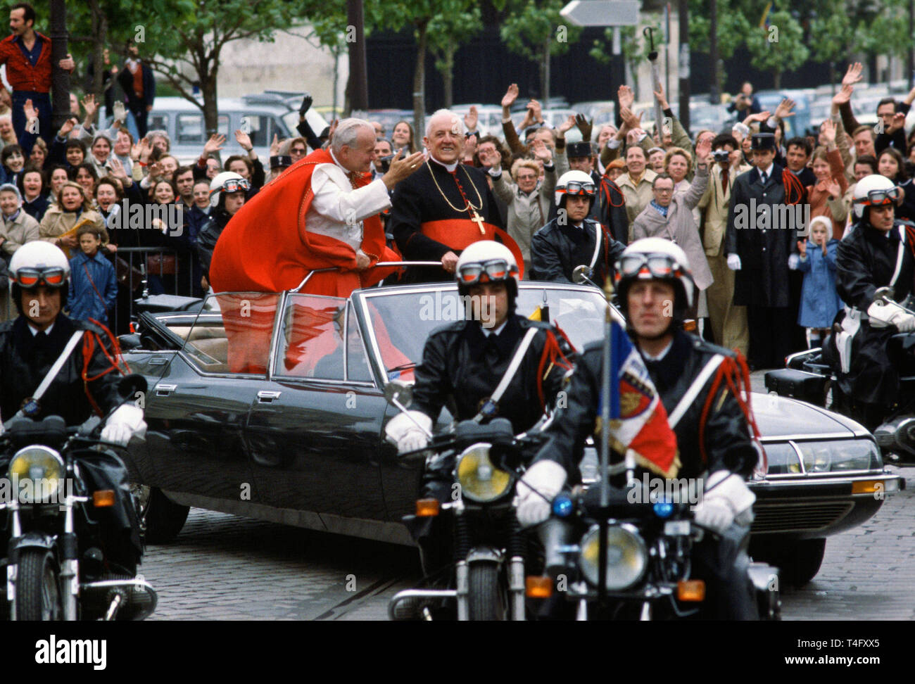 Pope John Paul II during his historic visit to Paris in 1980 travels in motorcade with light minimal security of open top car with police escort motorcycle outriders Stock Photo