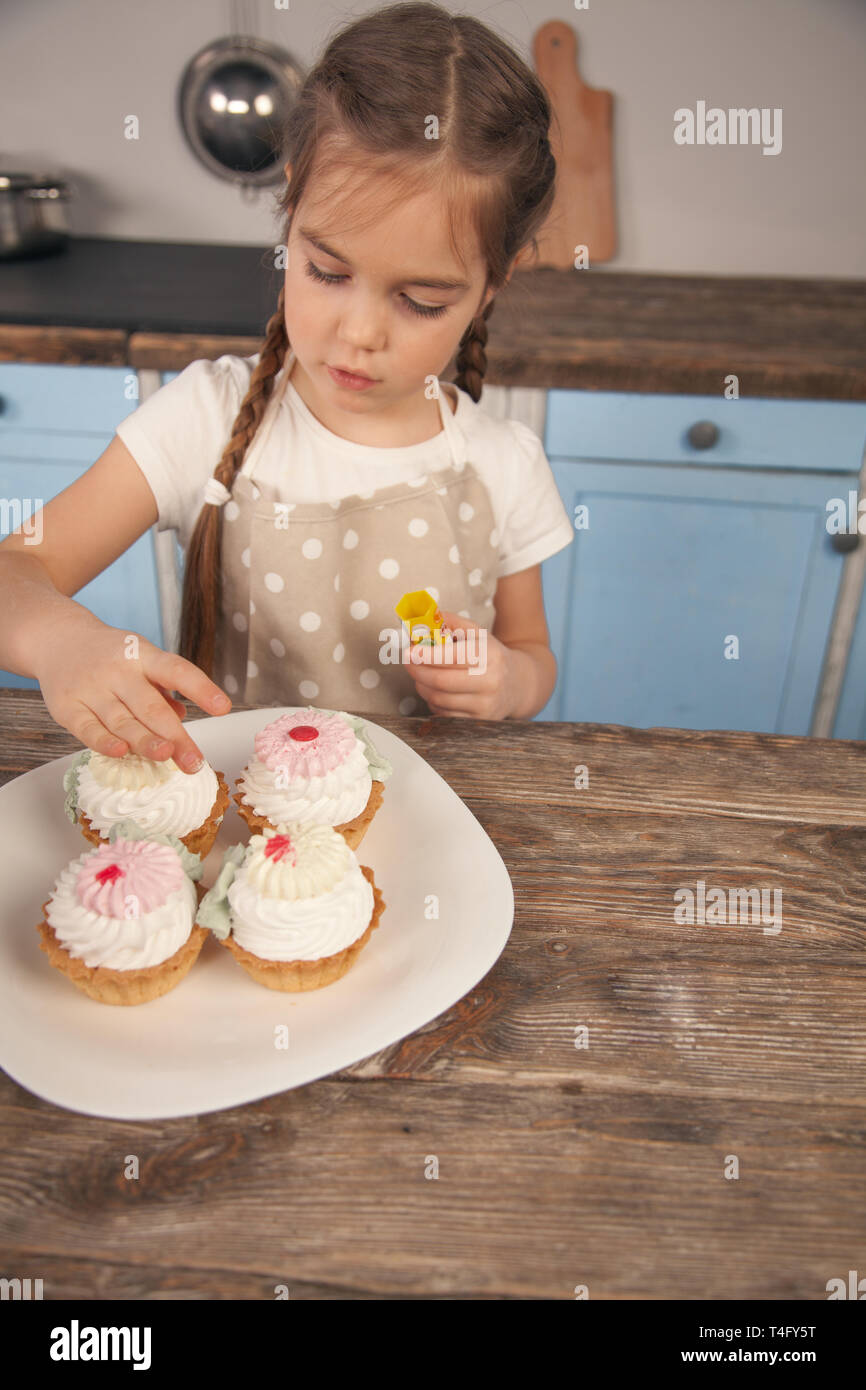 child daughter in the kitchen decorating cakes she is made with her mom. little helper, homemade food. Cakes are in the focus. Stock Photo
