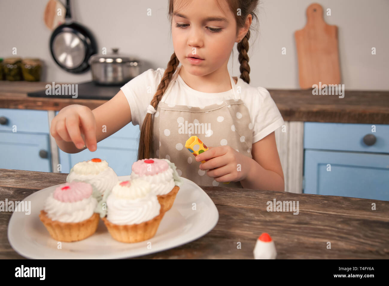 child daughter in the kitchen decorating cakes she is made with her mom. little helper, homemade food - Stock Image