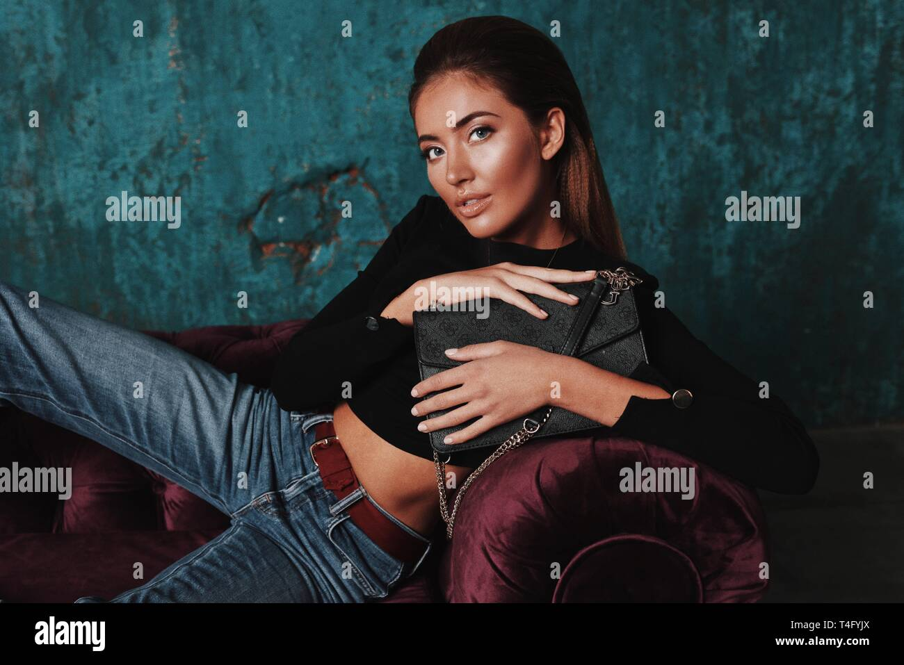 Portrait of amazing young fashion girl laying on the sofa, holding the black purse in her hands. Big lips, white teeth, long straight hairstyle.Modern Stock Photo