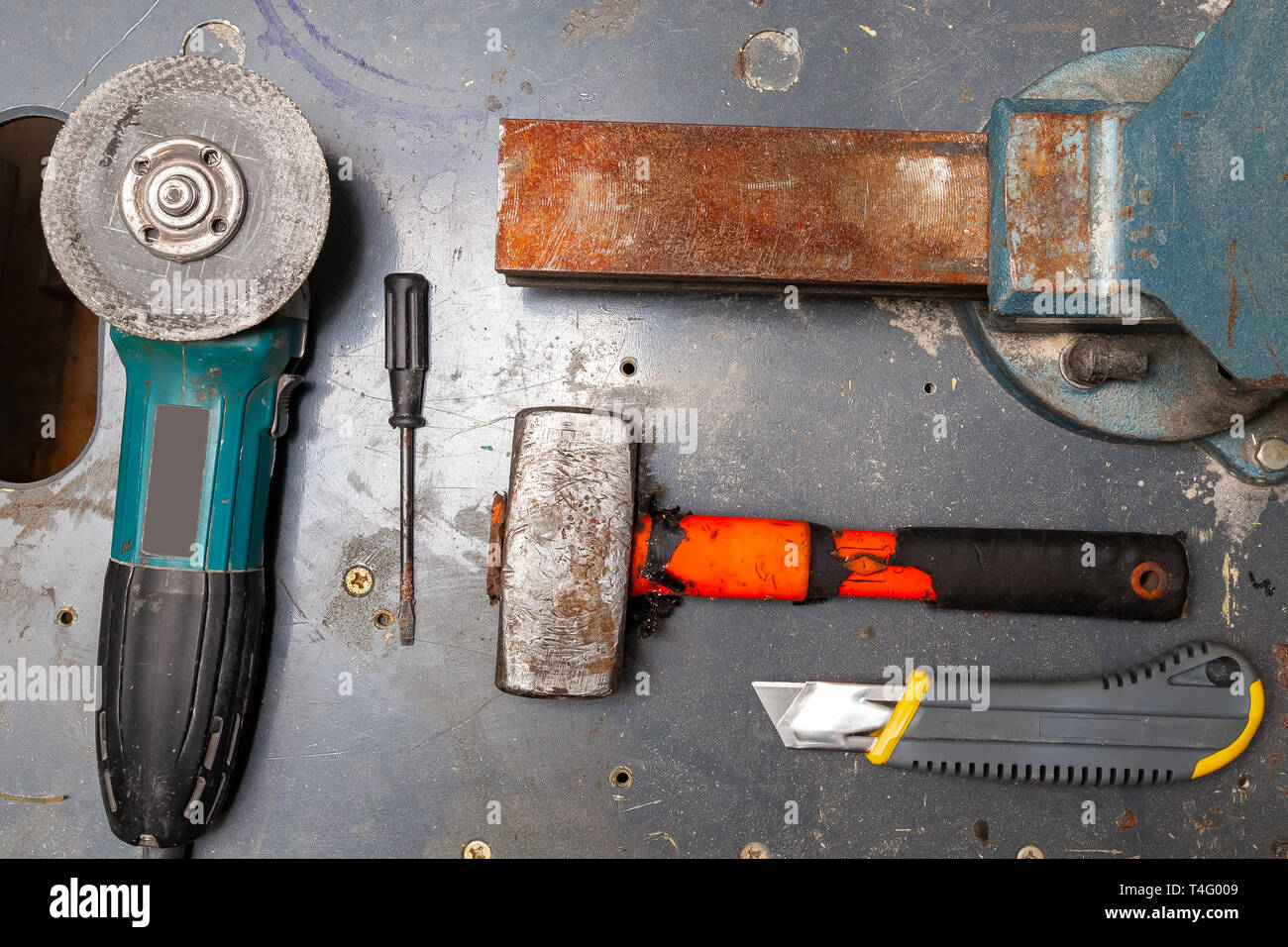 Flat lay view of a workbench with a set of tools consisting of a large heavy vise, angle grinder, screwdriver, cutter, sledgehammer, and a spare cutti - Stock Image
