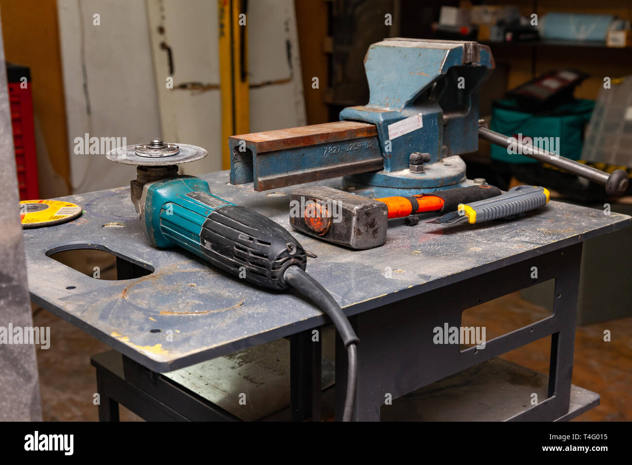 View of a workbench with a set of tools consisting of a large heavy vise, angle grinder, screwdriver, cutter, sledgehammer, and a spare cutting disc i - Stock Image