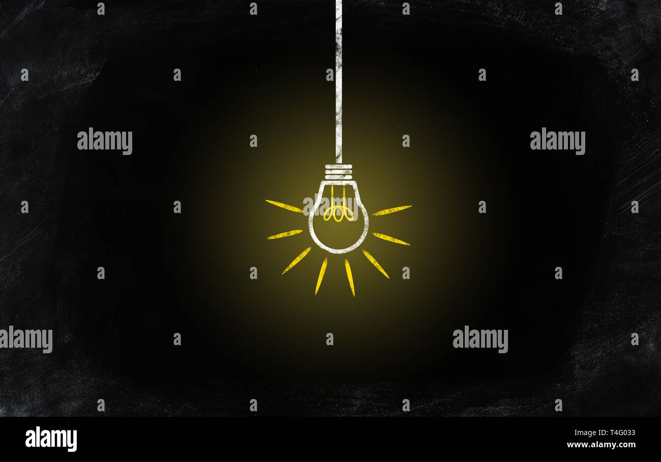 chalk drawing of brightly glowing light bulb in darkness on chalkboard - Stock Image