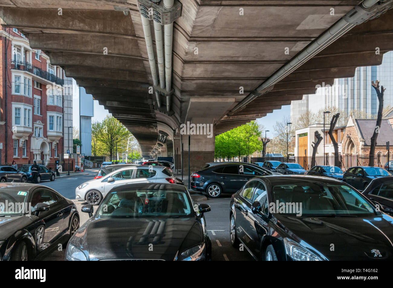 Cars parked under the Hammersmith Flyover. Built in 1960s, the flyover carries the A4 road in West London. - Stock Image