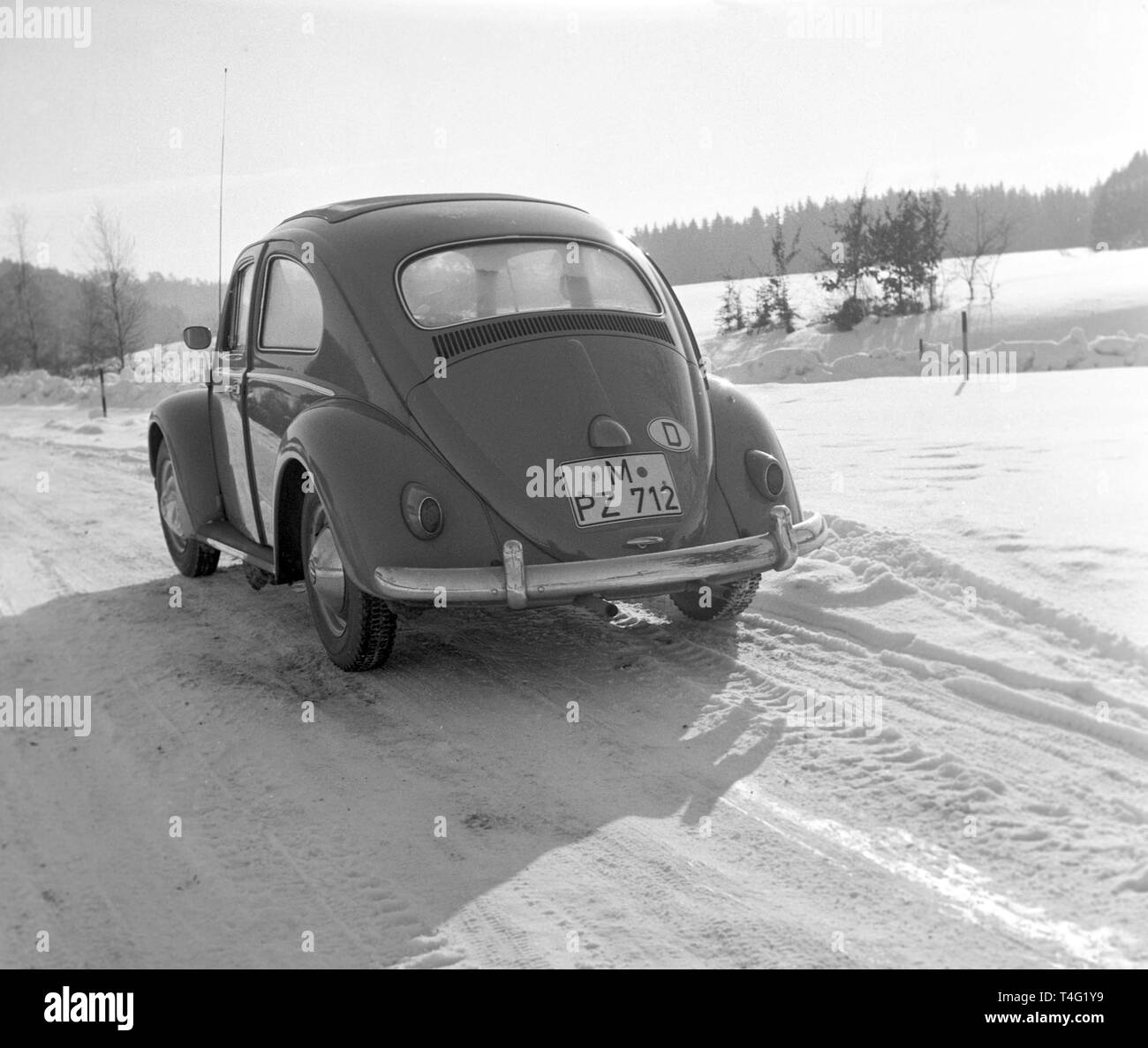 A VW-Käfer stands at the side of a snow-covered road (undated archive picture from January 1963). | usage worldwide - Stock Image
