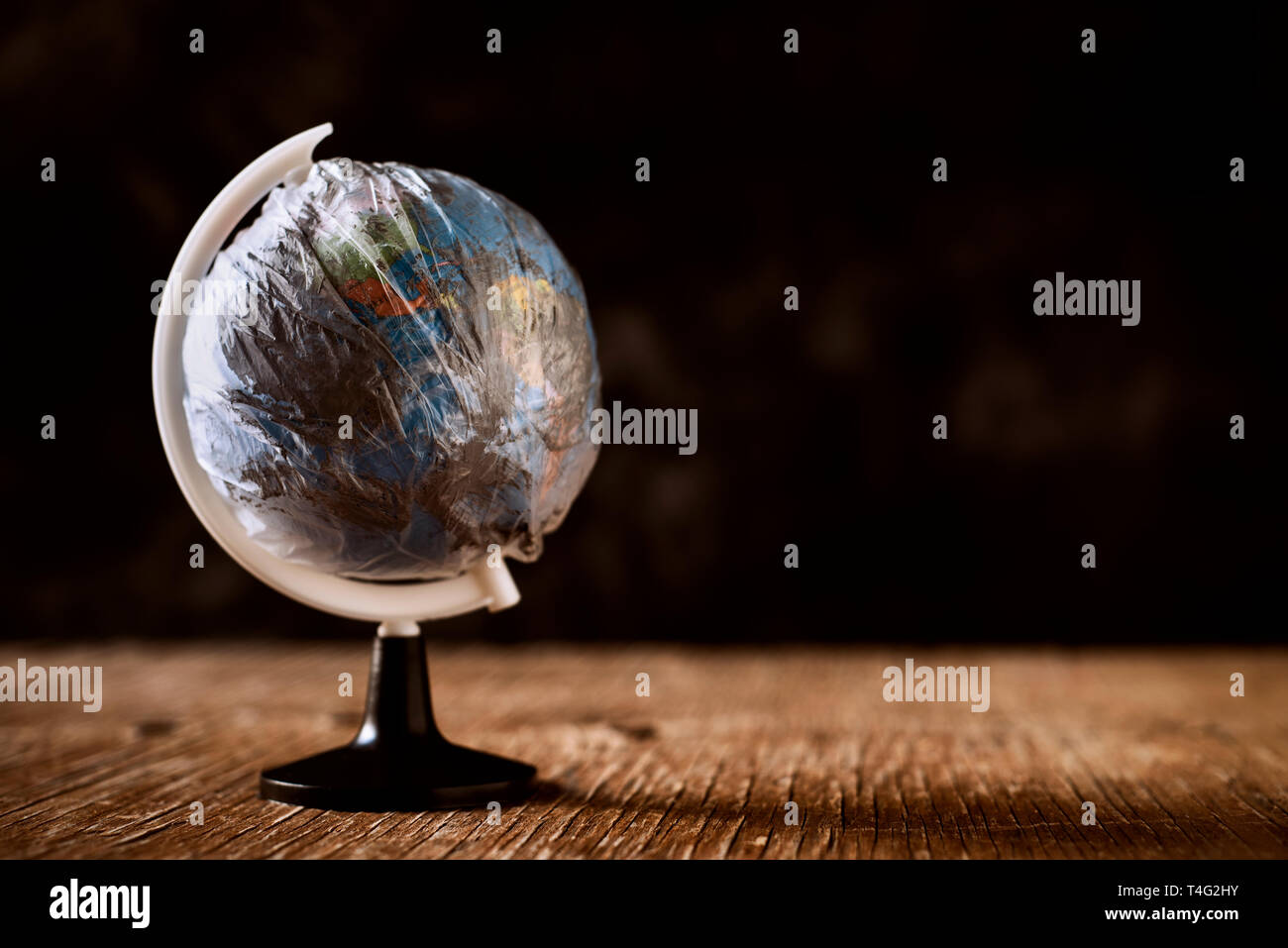 a world globe wrapped in a dirty plastic, on a rustic wooden surface, against a dark background, depicting the air pollution, the excess of plastic wa - Stock Image